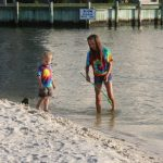 Two children search for crabs in the surf