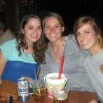 Three ladies pose with some tall drinks