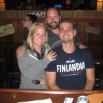 Three people pose at the Macky's wooden bar