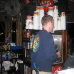 A bar tender works behind a bar
