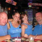 Two servers at Macky's pose with some customers all in blue shirts