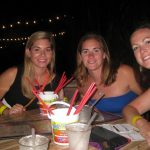 Three ladies with large drink buckets grin