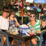 A family enjoys the sun outside of Macky's Bar and Grille in Ocean City MD