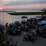 People eat dinner during a sunset on the bay