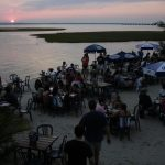 a sunset while people feast at macky's bayside