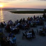 people dine at tables while the sun sets
